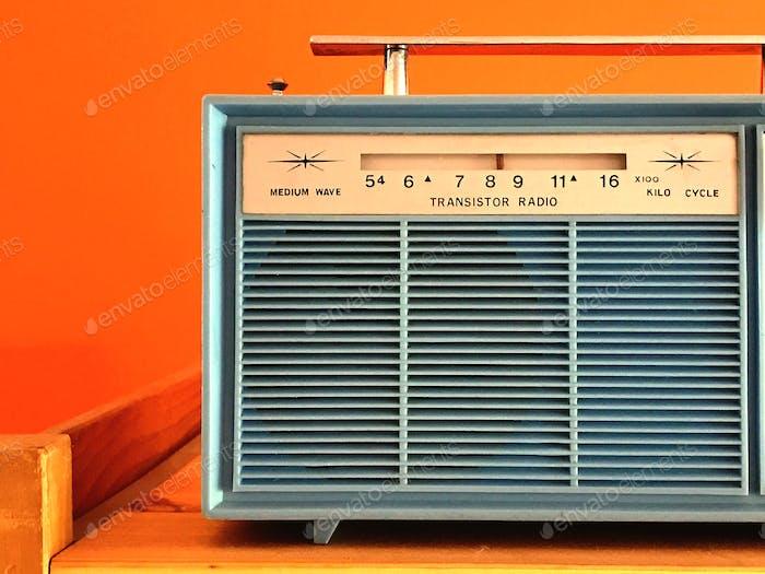 Old fashioned transistor receiver on orange background