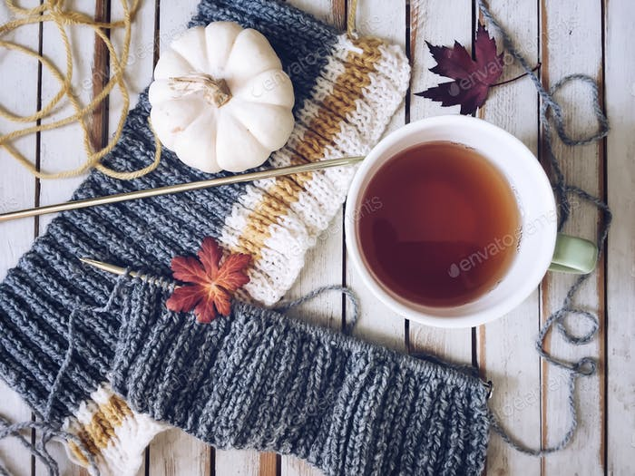 Overhead shot of a knitting project with a cup of tea, white pumpkin and autumn leaves 💲 ✨NOMINATED✨