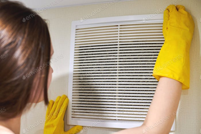 Holding ventilation grill of HVAC for cleaning or replacing.