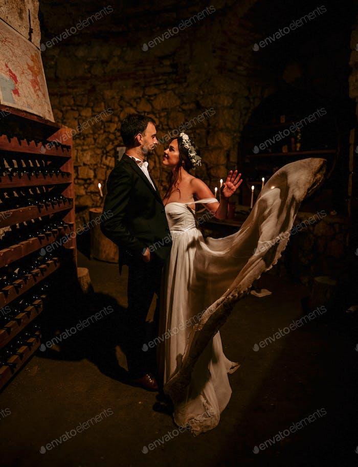 Retrato de jóvenes recién casados en bodega con luz de vela ambiental.