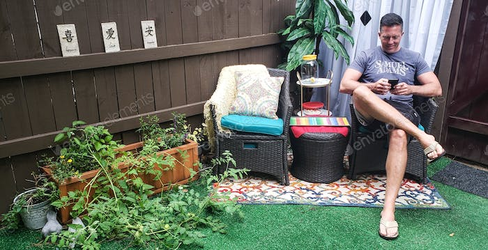 Active millenial enjoying some alone time enjoying his new patio arrangement due to mom and Aunt