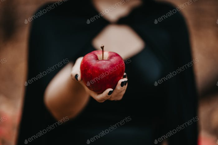 Woman as witch in black offers red apple as symbol of temptation, poison