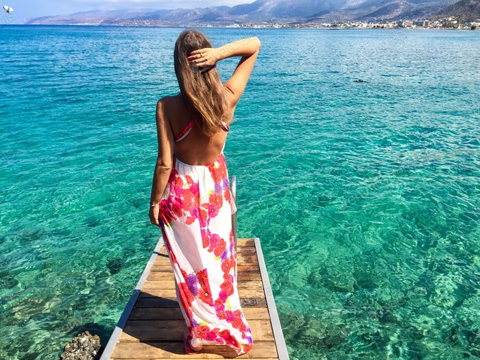 Sexy woman with long flower dress on the beach in Crete