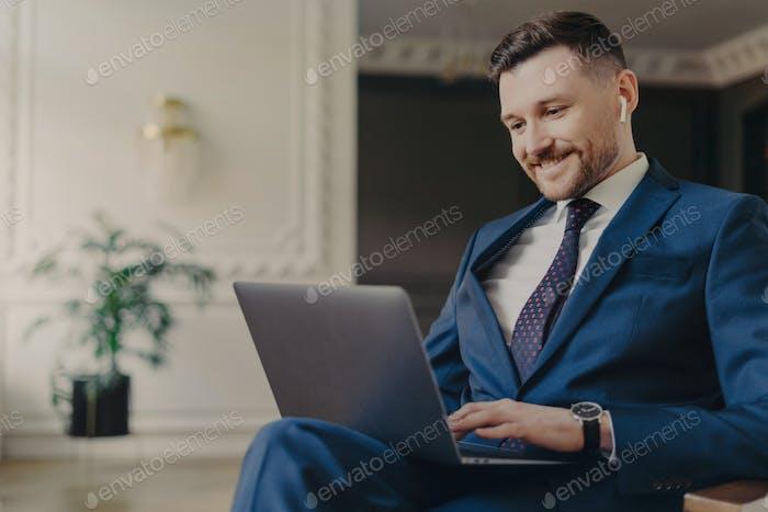Männlicher Unternehmer arbeitet an Laptop-Computer arbeitet remote hat Videokonferenz