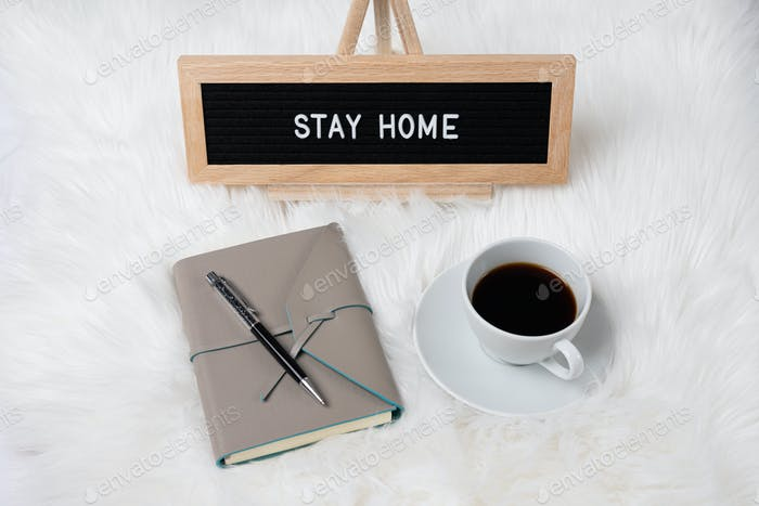 Stay Home sign with a notebook and coffee