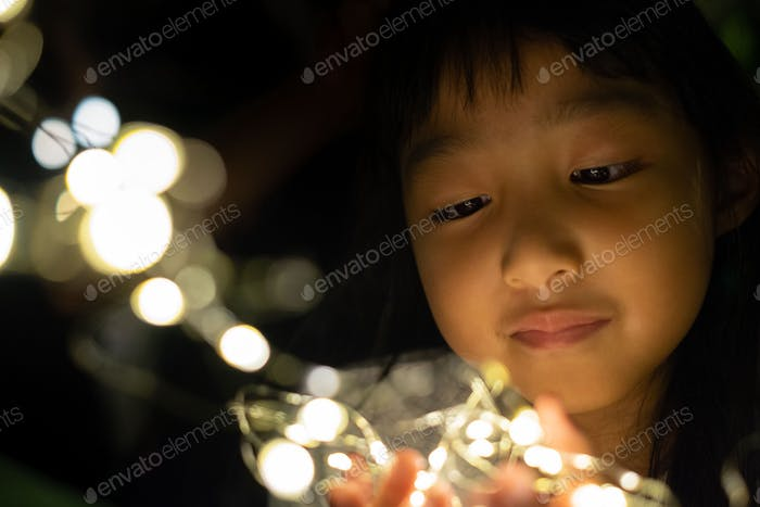 Head shot of a Thai little girl looking at light generated from small light bulbs with happy face