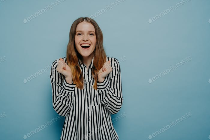 Smiling young woman being excited and celebrating success