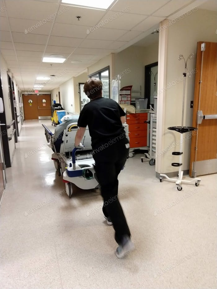A patient being pushed on a gurney through a hospital ER Emergency Room hallway with an IV
