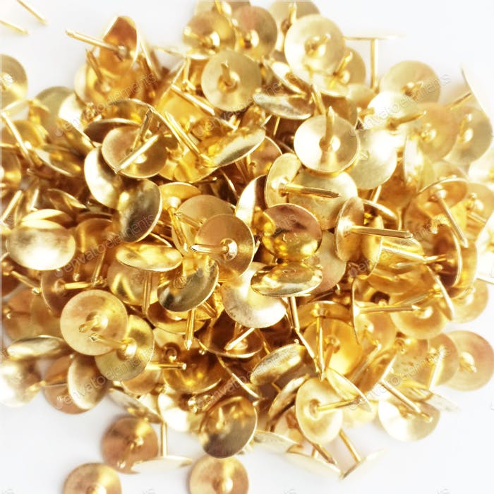 Detailed view from above of pile of gold tacks on a white background.