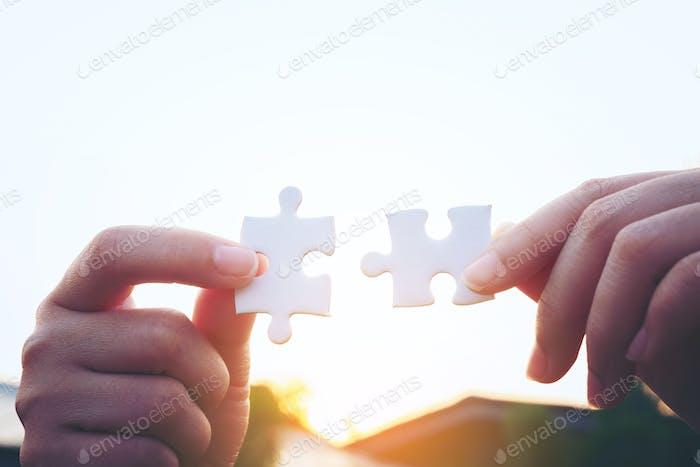 Primer plano de la mano de la mujer conectando rompecabezas con la luz del sol, símbolo de asociación y conexión