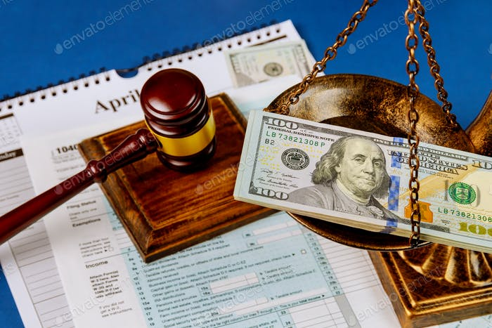 Hundred US dollar bills on a table scales of justice, gavel IRS form