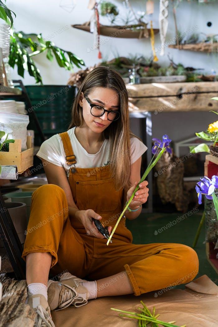 Florist Frau umgeben von tropischen Pflanzen schneiden den Stamm der Iris Blumen mit Gartenschere