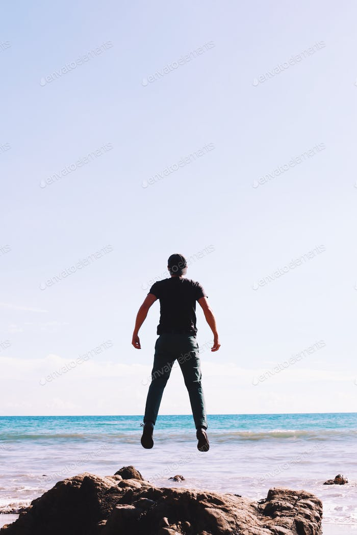 Young man jumping by the ocean