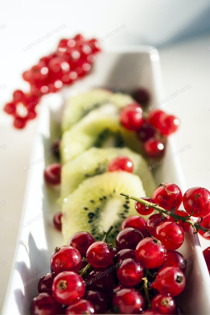 Scheiben von Kiwi und Trauben von roten Johannisbeeren in einem weißen Keramikboot auf weißem Hintergrund ⭐️ NOMINIERT