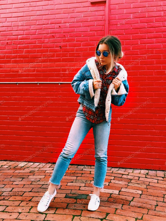Girl wearing blue denim Sherpa jacket and jeans, posing in front of red brick wall