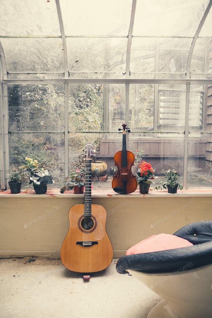 A guitar and violin sit near a window.