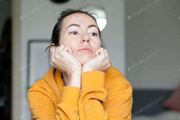 Eine junge Frau gelangweilt, trägt gelbes Sweatshirt, Langeweile, Emotionen, Melancholie, Denken, nach Hause