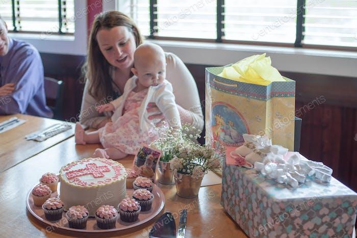 Familie feiert die Taufe des Babys mit einem Kuchen