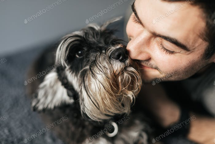 The owner hugs his little dog while lying on the couch.