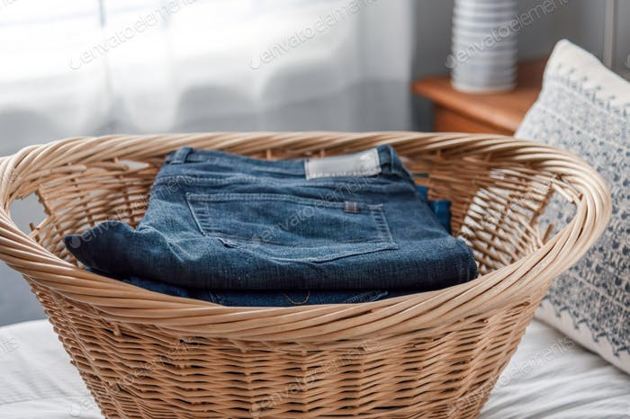 Neatly folded jeans in wicker laundry basket on the bed