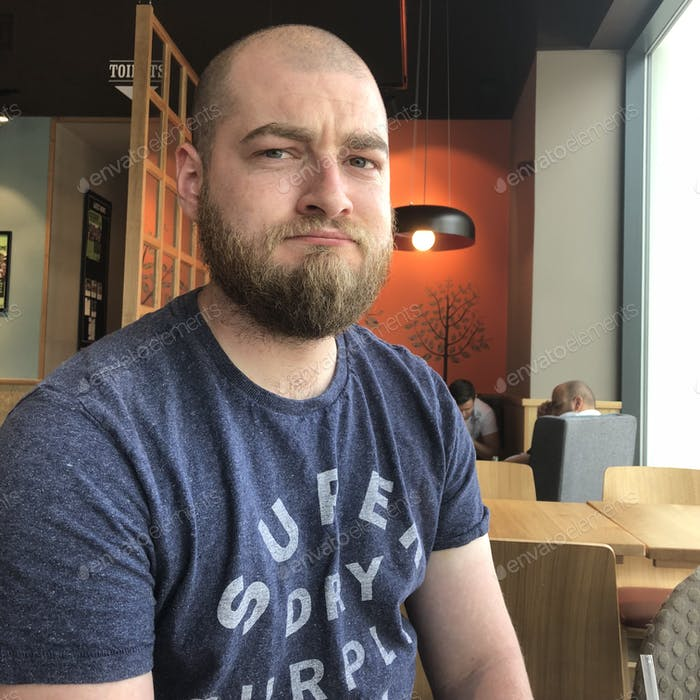 Frowning bearded millennial man
