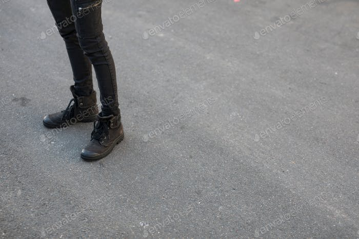 View of the legs of a young girl wearing skinny black yeans and cool chunky black boots against the