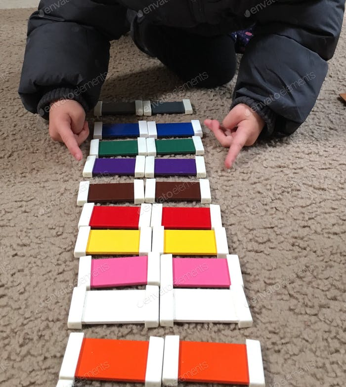 A child at a Montessori school is matching color tablets