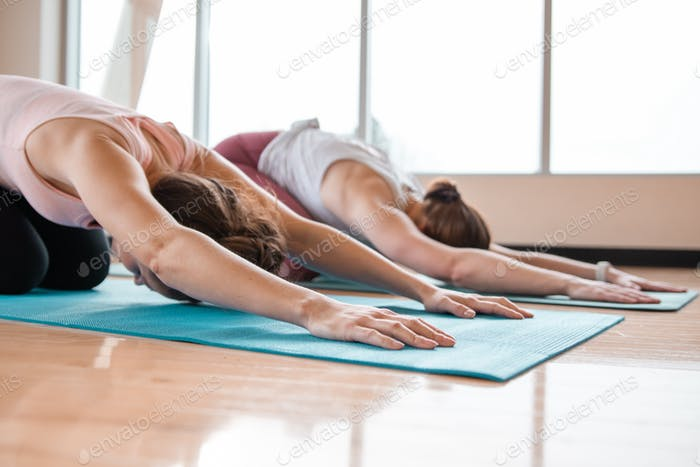 two women doing downward dog yoga position on mats in a brightly lit gym