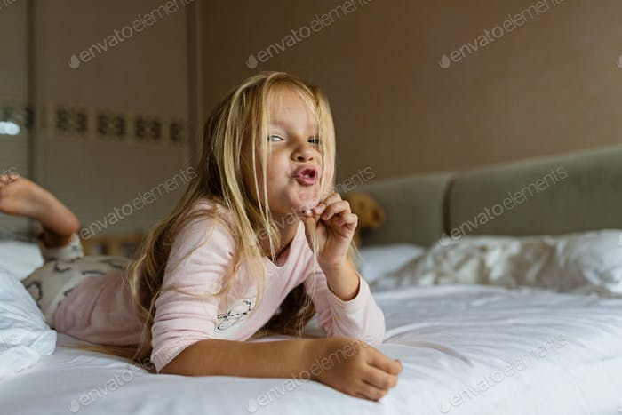 Nominated   Cute little girl with blonde hair lying on the bed in pajamas. Kids fun child childhood