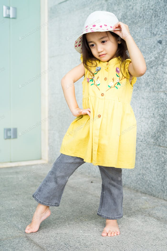Portrait of beautiful little gorgeus lovely toddler girl in mustard summer look clothes, fashion dre