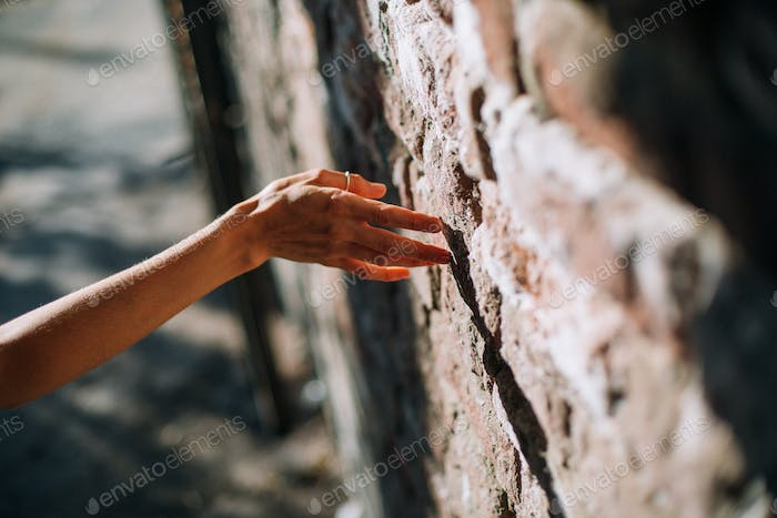 Woman's hand on a bricks wall background