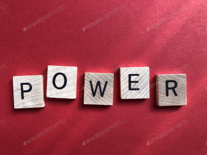 Power, word in 3D wooden alphabet letters isolated on a plain red background with copy space