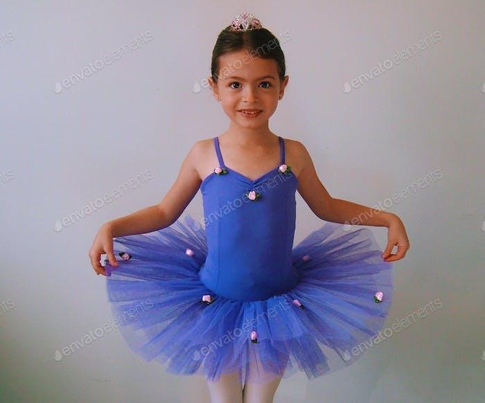 Kleines Mädchen im blauen Ballett-Tutu posiert für ein Bild