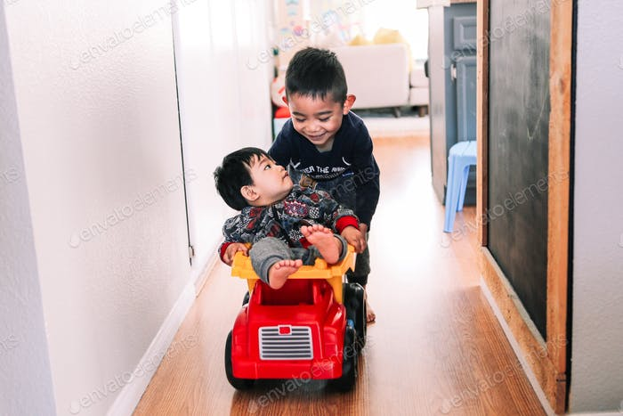 Older brother pushing his younger brother through a hallway at home while riding in a toy truck.