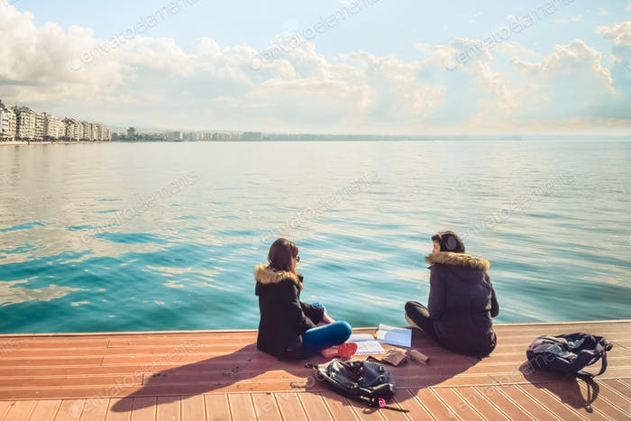 Two Friends Teenager Student Girls Reading Their Books And Talking Outdoor In Front Of The Sea At Po