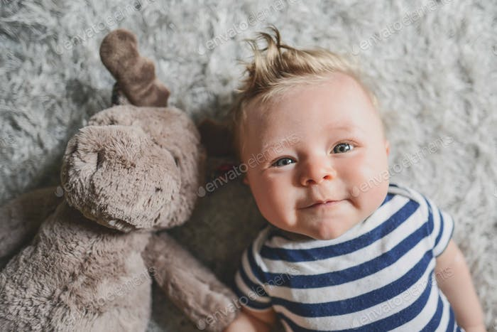 Portrait of cherub faced chubby cheeked caucasian baby with blue eyes and blonde hair and red cheeks