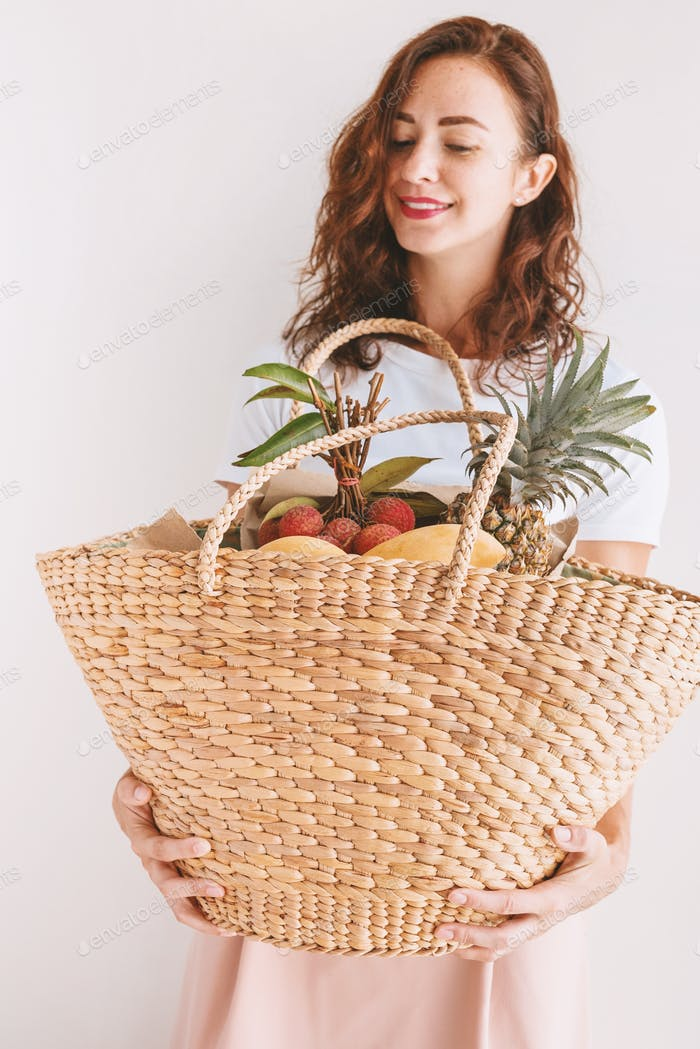 Young woman standing with fruits in wattled bag near wall. Style kinfolk. Pastel colors. Natural, ec