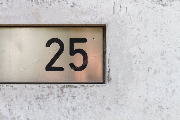 The number twenty five on a metal plate