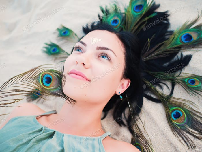 Portrait of beautiful woman with flash tattoo and peacock feathers in hair lying on beach