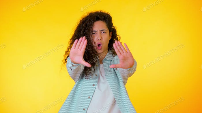 Angry annoyed woman raising hand up to say no stop