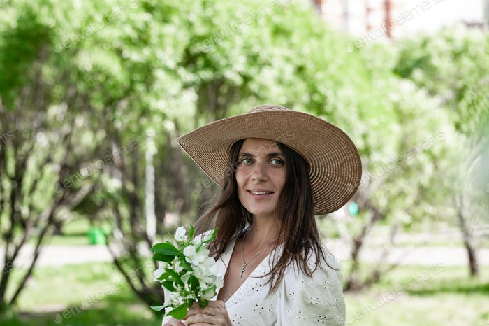 Pretty and happy female is posing in straw hat on the spring park.