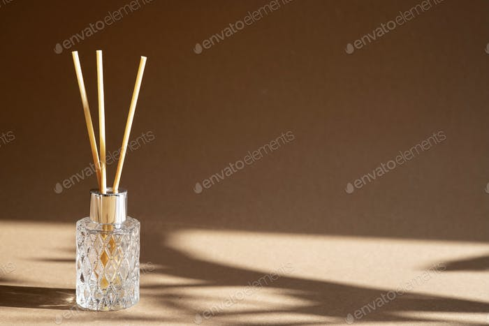 Aromatic reed air freshener on brown background hard shadow. Aromatherapy sticks.
