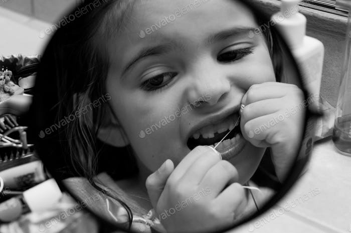 Young girl flossing teeth in mirror