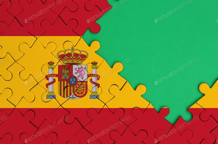 Spain flag  is depicted on a completed jigsaw puzzle with free green copy space on the right side.