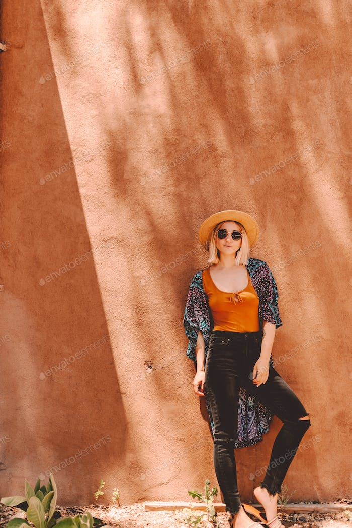 Woman in authentic outfit stands in front of orange brown clay wall in Santa Fe.