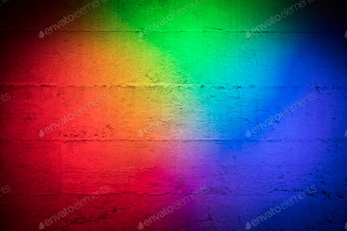 Coloured primary colored lights red blue and green on a textured concrete wall as background stage p