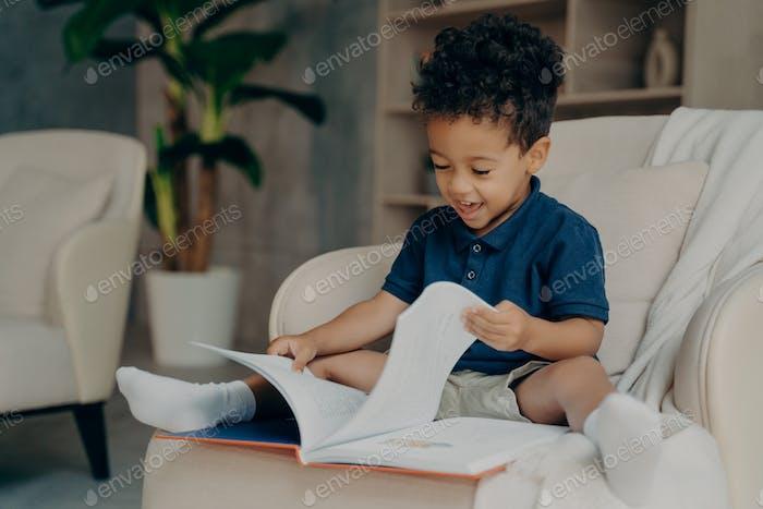 Feliz niño de raza mixta con lindo libro de lectura de pelo rizado en casa