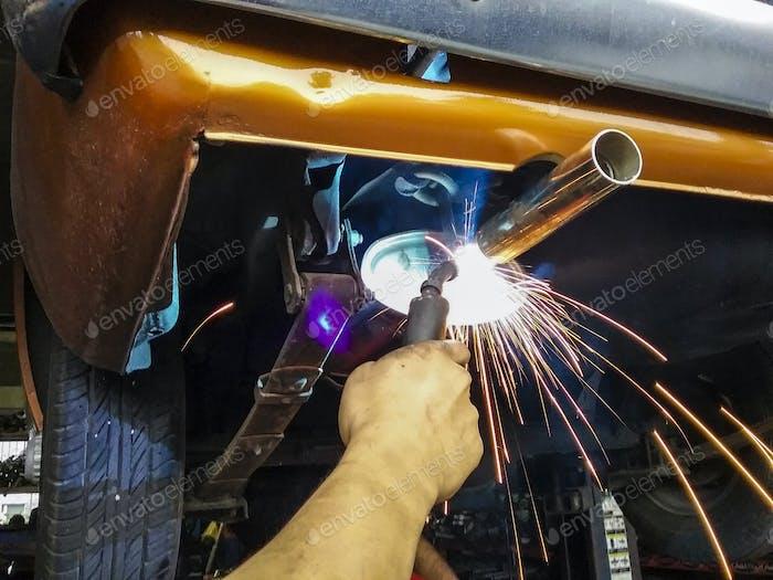 Closeup of blue collar worker welding classic car muffler