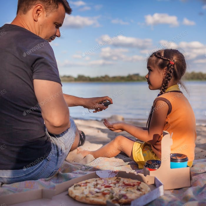 Vater und Tochter Anwendung von Alkohol Spray auf die Hände vor Mini-Picknick, persönliche Hygiene