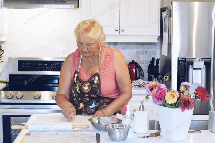 A woman is baking in a bright white modern kitchen.  Seniors lifestyle  ✨NOMINATED✨
